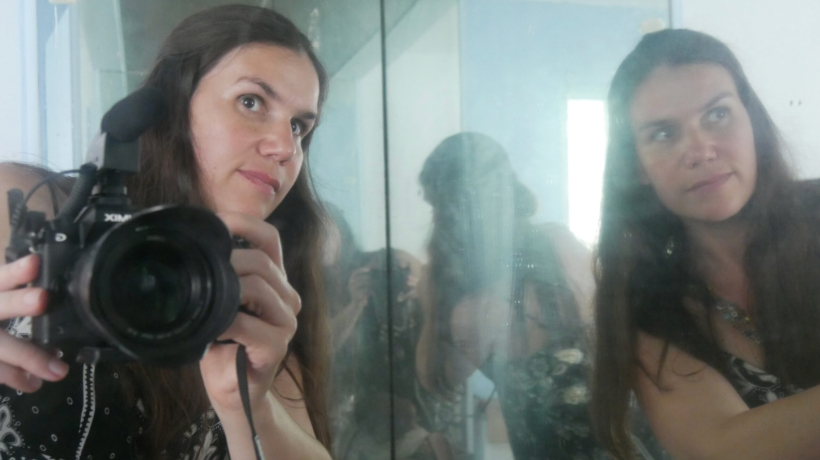 Alexandra Hidalgo filming herself in her father's mirror in A Family of Stories